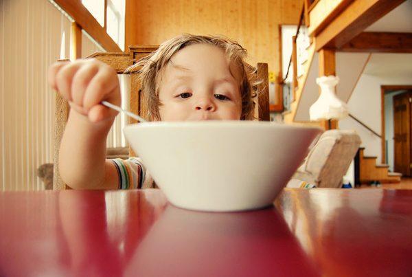 малко дете наднича в купа с храна и бърка с лъжица