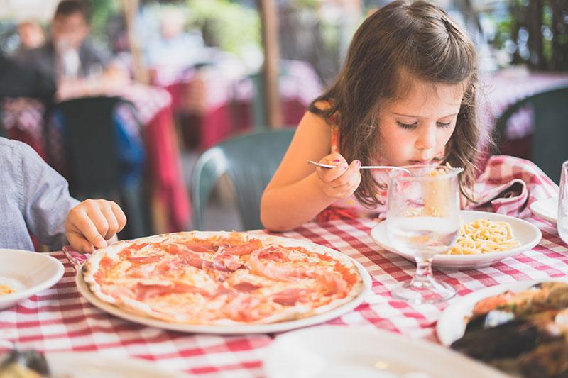малко момиче се храни със спагети и пица