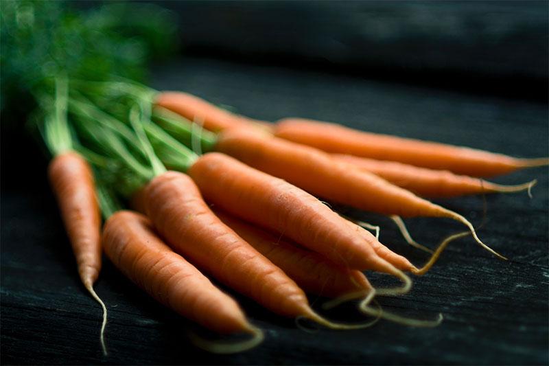 връзка моркови върху тъмна маса