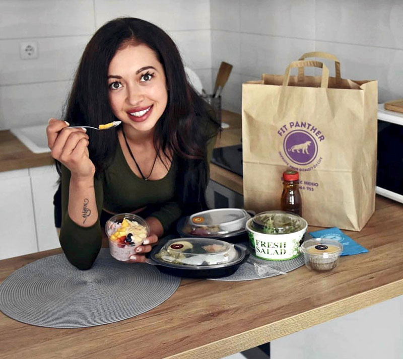young girl is eating healthy food from Fit Panther's kitchen