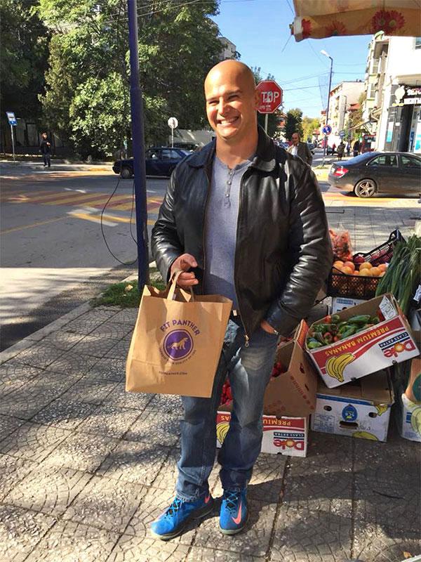 усмихнат клиент с плик храна от Fit Panther пред магазин за плодове и зеленчуци