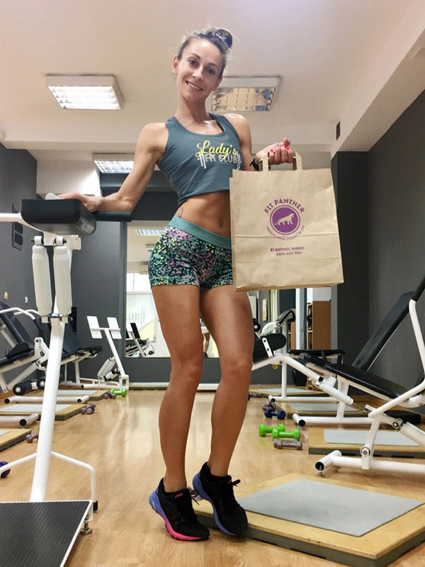 female client with a pack of healthy food from Fit Panther in the sports hall