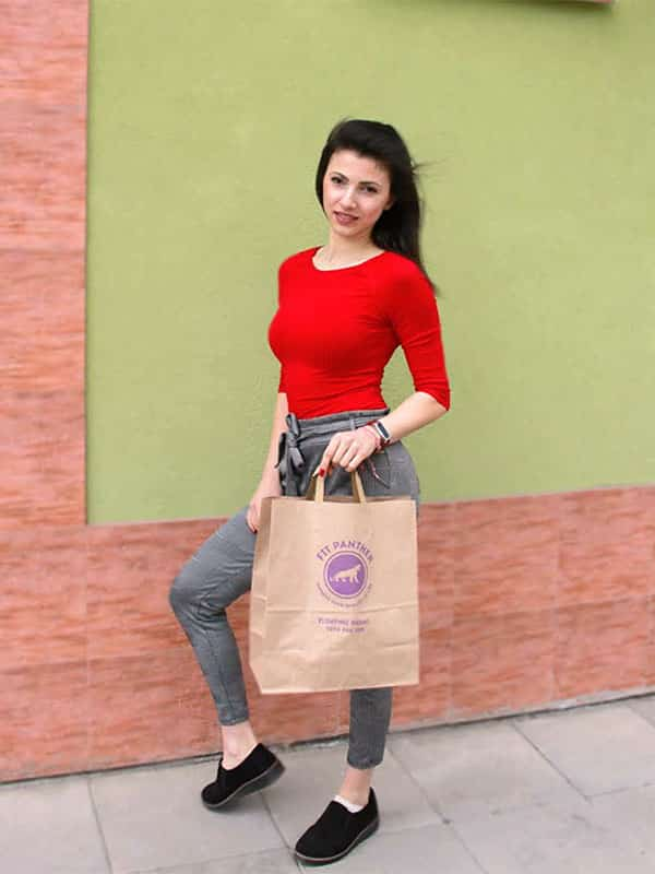 young woman with a package with healthy food from Fit Panther