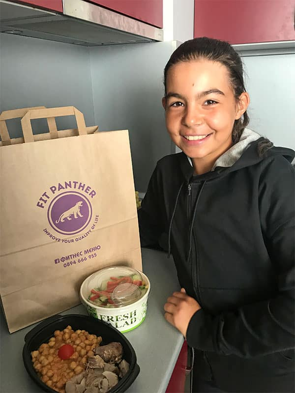 young girl in the kitchen with boxes of healthy food from Fit Panther