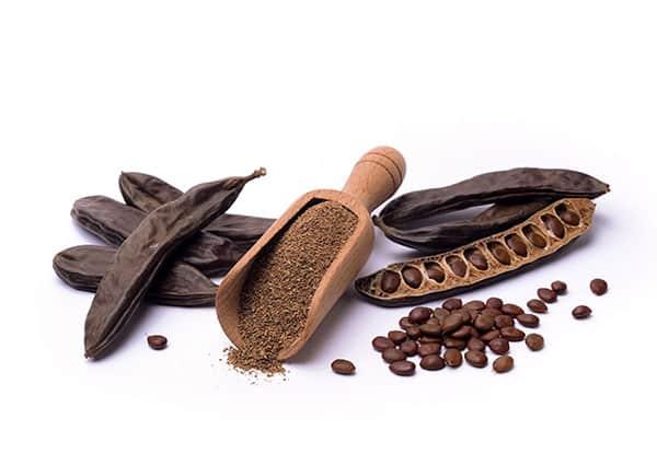 семена и брашно от рожков на бял фон с дървена лъжица