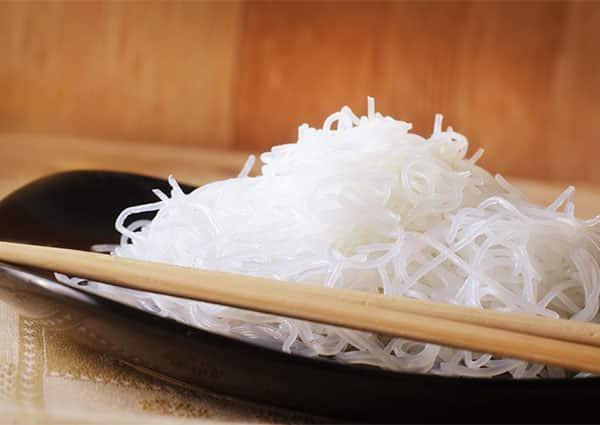 оризови спагети, поднесени в черна чиния