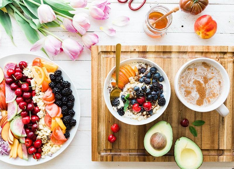 закуска с плодове и авокадо въху дървена дъска и чиния с плодове цветя и мед
