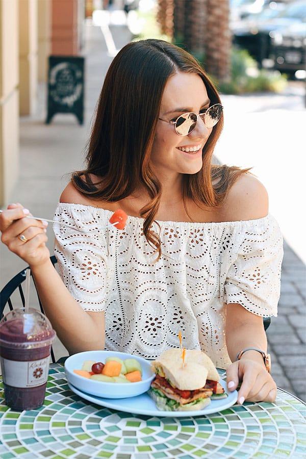 млада дама закусва сандвичи с плодова салата
